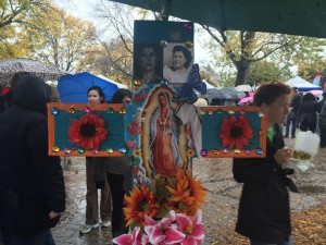 A cross decorated with flowers, Mother Mary, and photos of lost loved ones stood among onlookers at Walker's Point's Dia De Los Muertos Celebration | Photo credit: Mary Jo Contino