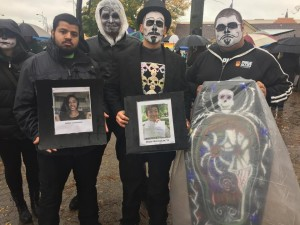 [Left to right] Michael Freytes, Emilio DeTorre and Julio Guerrero stand with a painted coffin and photos of teens that have committed suicide because of bullying. | Photo credit: Mary Jo Contino