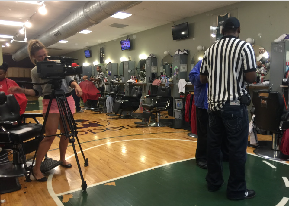 Student Rebecca Papenthien shoots video at a Milwaukee barbershop.